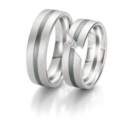 Niezwykłe obrączki ślubne z białego złota z delikatną linią i lśniącym brylantem między krawędziami