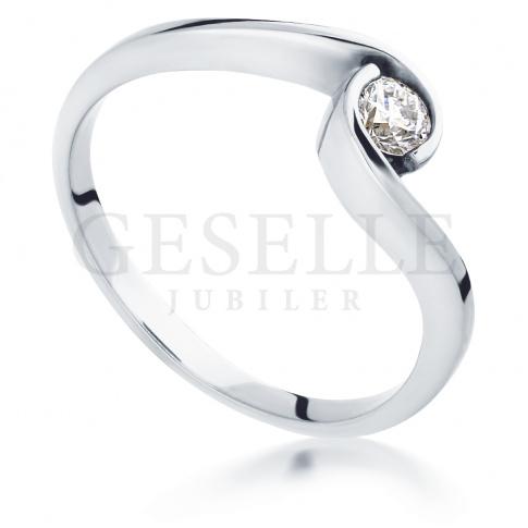 Symbol miłości z białego kruszcu - pierścionek zaręczynowy z pełnym blasku brylantem 0.15 ct