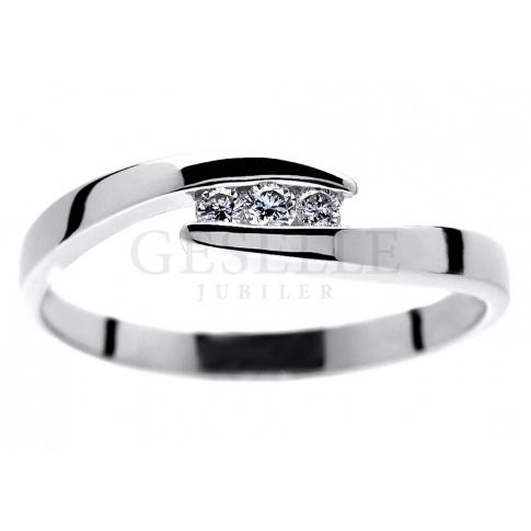 Delikatny pierścionek zaręczynowy z białego kruszcu z trzema brylantami 0.06 ct