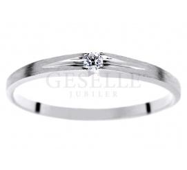 Delikatny pierścionek z białego złota próby 585 z lśniącym brylantem o masie 0,03 ct