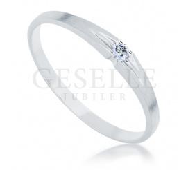 Delikatny pierścionek z białego złota próby 585 z lśniącym brylantem o masie 0.03 ct