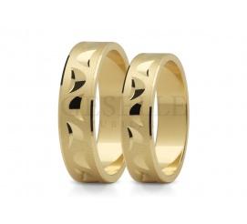 Elegancki duet obrączek ślubnych z klasycznego złota z delikatnymi nacięciami