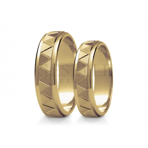 Złote obrączki ślubne z klasycznego żłótego kruszcu powierzchnia przyozodobiona geometrycznym wzorem