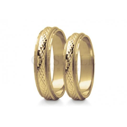 Zachwycające obrączki do ślubu wykonane z złota, przez środek biegnie wspaniale zdobiona lśniąca obręcz