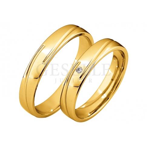 W klasycznym stylu - damska obrączka z żółtego złota z delikatną linią i pełnym blasku brylantem