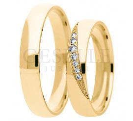 Duet  klasycznych obrączek ślubnych wykonany z żółtego złota zwieńczony wstęgą kamieni w oprawie jubilerskiej