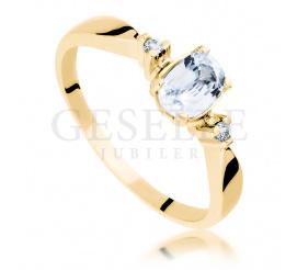 Magiczny pierścionek z białym szfirem w towarzystwie brylantów wykonany z żółtego złota pr. 585