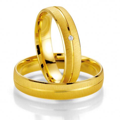 Nieprzeciętne obrączki ślubne matowe z żółtego złota z jednym lśniącym brylantem